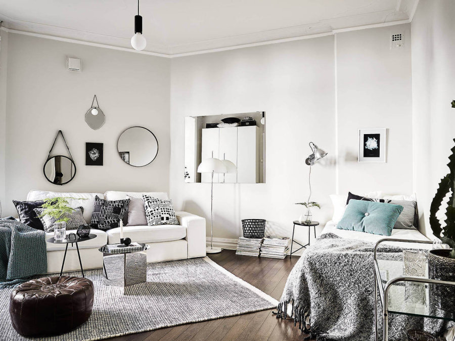 フローリングの色がダークブラウンでソファーはホワイトのソファーを使用しています。ライトグレーのラグマットにクッションでアクセントを持ってきています。ミラーもたくさん付けていて部屋が広く見えます。