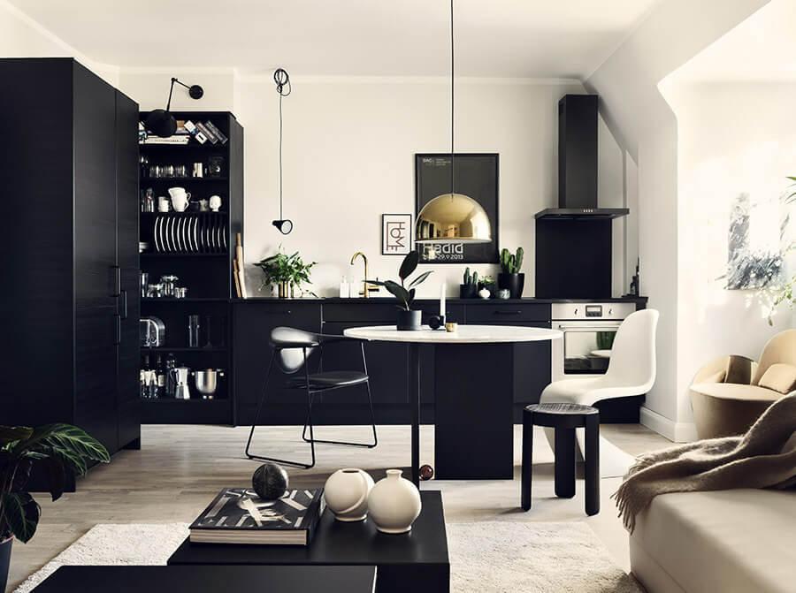 ブラックのキッチンが空間をシックにしているインテリア画像。ランプのシェードがゴールドで個性的でおしゃれな印象。