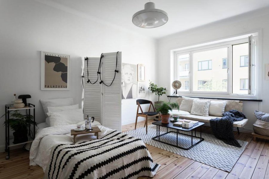 ナチュラルブラウンからのフローリングにソファーとシングルベッドが置いてあります。ベッドの横に白い衝立が立ててあり空間を仕切っています。ソファーにはアームがないので圧迫感がありません。