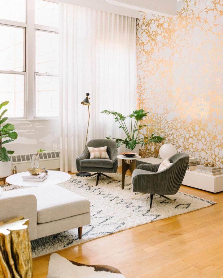 明るいフローリングにモスグリーンのリビングチェアがコーディネートされた空間です。壁面は金箔のような壁面で個性的ですね。ラグマットは白色で窓の前で非常に明るい空間です。白いリビングテーブルも全体のバランスを整えています。