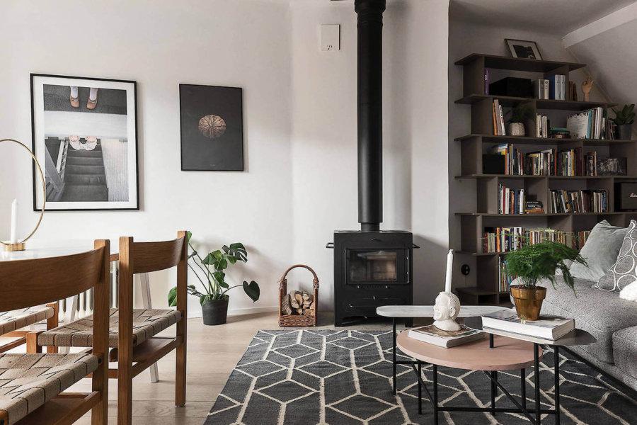 明るい色のフローリングにライトグレーのソファーと黒い暖炉がアクセントになっています。ヨーロッパの海外インテリアでは暖炉はよく登場します。幾何学模様のラグマットも登場回数が多いですね。