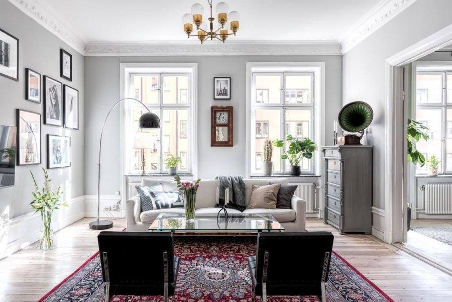 明るめのフローリングにホワイトのソファーを置いています。正面に整体するようにブラックのリビングチェアが2脚配置してあります。印象としてはかなりフォーマルな印象です。赤い絨毯が個性的です。