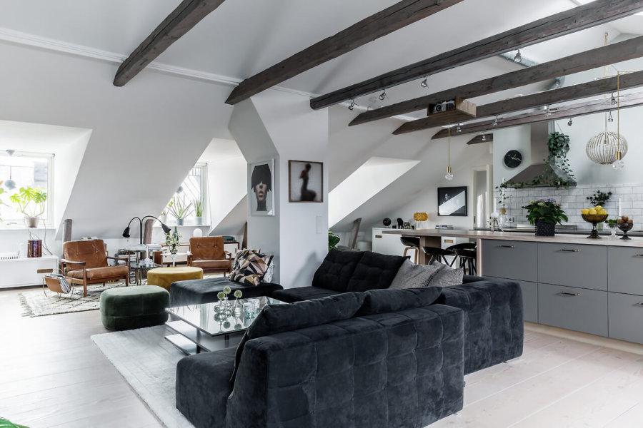 勾配天井に光が入る工夫をして明るさをキープしています。ダークグレーのソファーとキャメルのリビングチェアは別々のリビングルームとして機能させているみたいです。