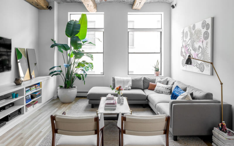 コーナーソファーを部屋の行き止まりに配置することで空間を広く見せています。観葉植物も背が高くインパクトがあります。招かれたゲストの視線が観葉植物に向くようにしていると思われます。アイキャッチが奥にあることで部屋に奥行きを感じさせることができます。