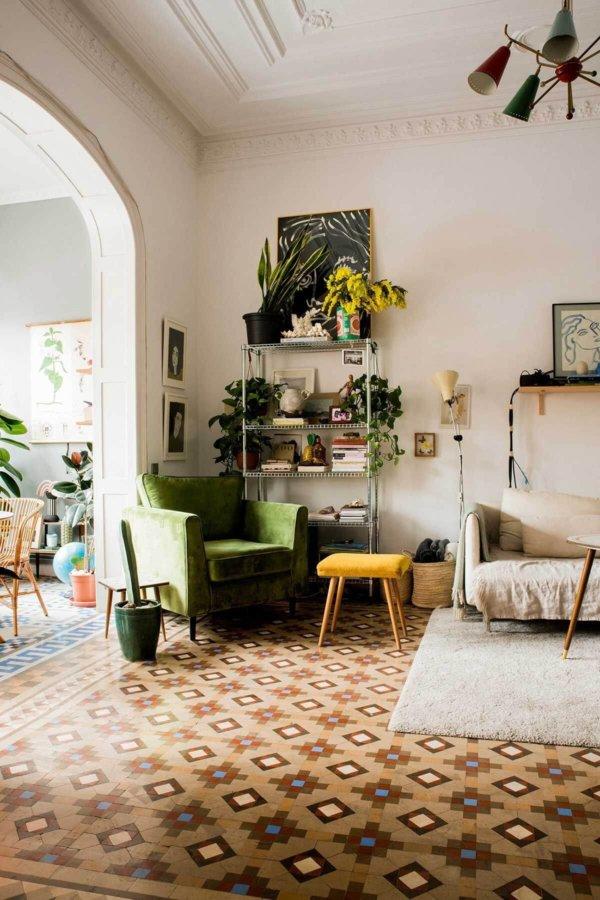 ブラウン系のタイルを敷き詰めています。ソファーはグリーンとアイボリーです。入り口がアーチ形をしている海外のインテリア事例です。タイルを使ってデザインされていて絨毯を敷いているような印象です。