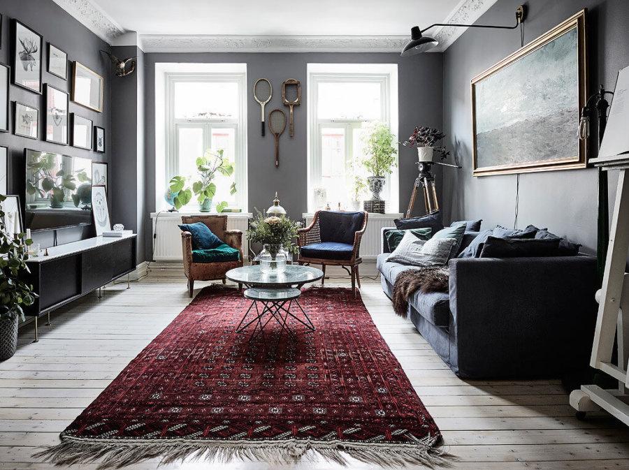 フローリングにネイビー系のソファーを配置して絨毯は赤色です。中東方面の絨毯を使用しており空間にぬくもりを感じることができます。