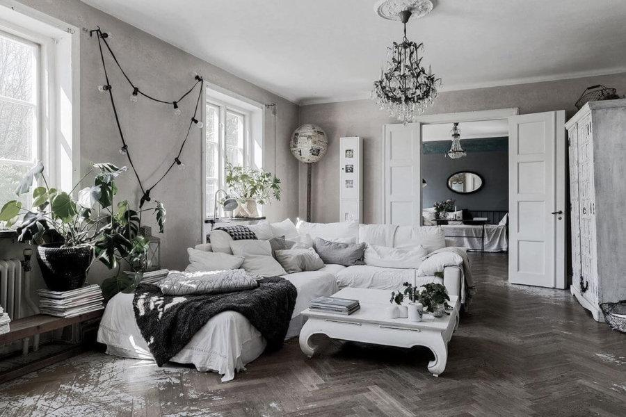 かなり使い込んだグレーのヘリンボーン柄の床と白いソファーのインテリアイメージ。