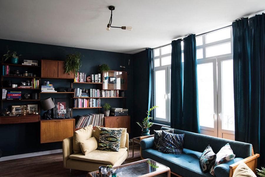 ダークブラウンのフローリングにブルーノソファーとグリーンとブルーの中間のような色の壁面に木目の家具が置いてあります。ミディアムブラウンカラーとブルーは海外インテリア事例ではよく見られるコーディネートです。カーテンまで統一してやるのはかなり徹底されている感じです。