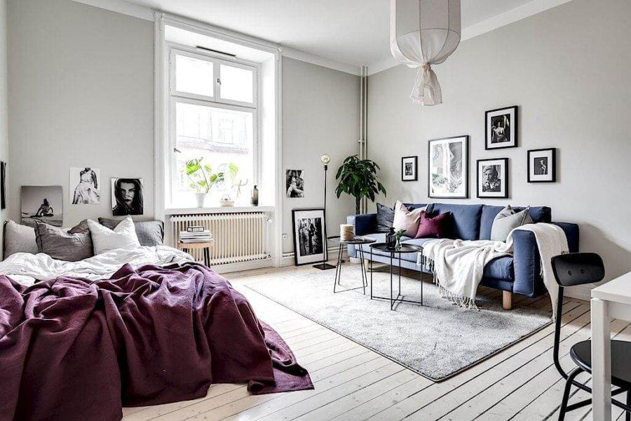 ホワイトフローリングにネイビーのソファーとパープルのベッドメーキングです。ソファーの上にもパープルのクッションが配置されていてお互いが尊重しあっている印象です。