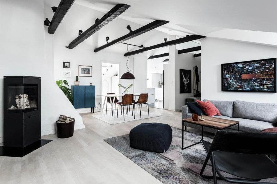 勾配天井になっていて開放感がある空間です。梁の色をブラックで塗装し暖炉の色と統一させています。男性的なインテリアになっています。