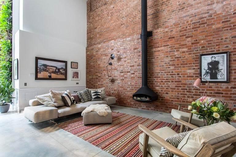 インテリアデザイナーAndrea Larsson Sanchezは、洗練されたコンクリート床、オリジナルのCrittall窓、現代的な家具とグラフィックテキスタイルの露出したレンガを補完します。