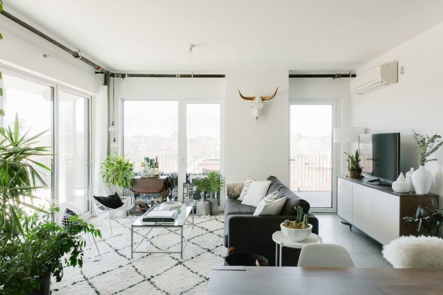 外の景色をゆっくりと眺めることが出来るように空が窓を向いて配置されています。ラグマットも広めにしていますね。窓の近くに観葉植物をたくさん置いています。テレビボードはソファーの背面に置いています。テレビの重要性は昔よりも高くないのかもしれません。