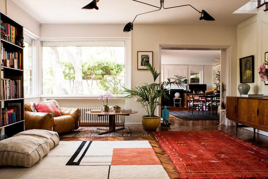 フローリングは使い込まれた古い木材を使用しておりヘリンボーンです。床にキリムを敷いています。リビングチェアを部屋の角にさりげなく置いています。木製家具はミディアムブラウンカラーです。