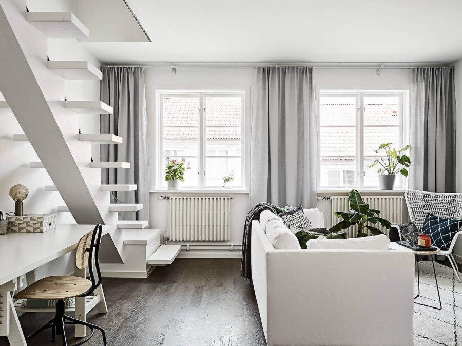 フローリングの色はグレーに近いようなダークブラウンからです。ソファーはホワイトでラグマットもホワイトです。カーテンはライトグレーを使用しています。窓が2つあり窓の下にはオイルヒーターが設置されています。デスクの色もホワイトで統一されています。階段のデザインも個性的ですね。