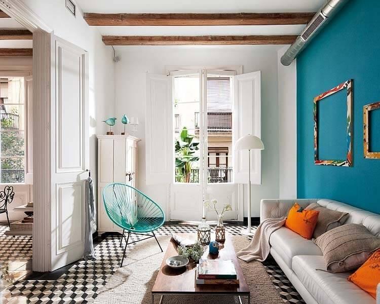 こちらのタイルはもう少しきめが細かいですね。壁面はブルーの壁面でソファーはホワイトのレザーソファーを使用しています。オレンジ色のクッションがアクセントカラーになっています。リビングテーブルはウォールナットです。