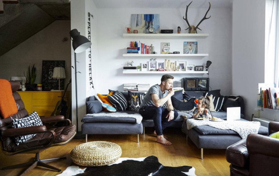 明るい床のフローリングにグレーのソファーでクッションをたくさん置いてコーディネートしています。壁面の白い棚にいろいろ飾ることができるので自分によってコーディネートを変えることができます。日本人はあまり使いませんがフロアランプは必須アイテムです。