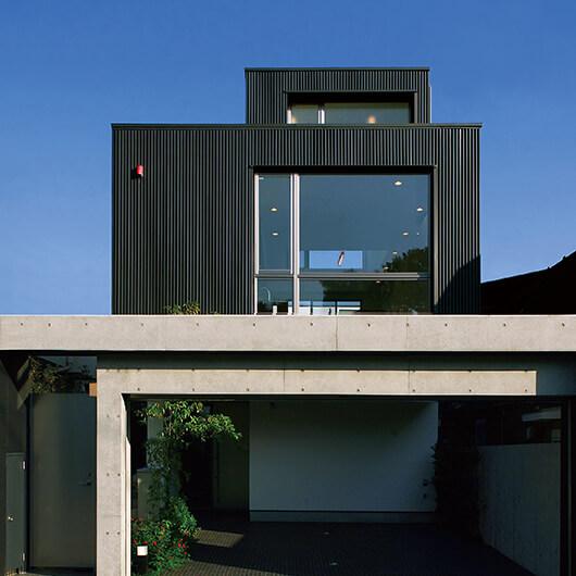 敷地約51坪。箱を連続された巧みな遠近法を持つ佇まいは、期待感を抱かせるに充分。前面はコンクリート打ちっぱなしのゲート。四角ばった全体の造形をさらに引き締める強いプロローグとなっています。ゲートは二重構造で内側を真っとブラックで塗装、陰影を持たせ、建物のガリバリウム鋼板の黒につないでいます。対照的に1階部分はイタリア製の白い塗り壁で仕上げ、全体が重い印象にならないようにモノトーンのコントラストでまとめました。