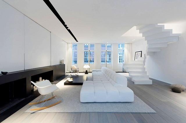 ここでは、デザイナーはより軽い側面に焦点を当てました。白いリビングルームの家具と、部屋の拠点となる黒いアクセントのハーフウォールが付いています。木製の床の熱帯の色調は、部屋が圧倒されるのを防ぎ、スカンジナビアスタイルの椅子は、現代的な快適さのオーラを加えます。